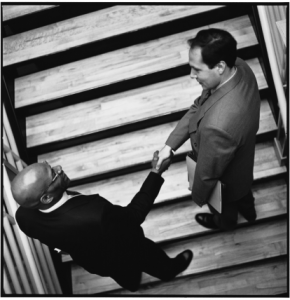 Image of two businessmen shaking hands on the stairs