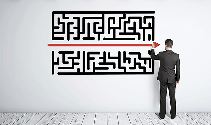 Man stands in front of a picture of a maze and has drawn a red line through the centre of it.