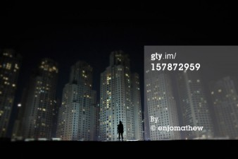 Man standing in front of skyscrapers at night