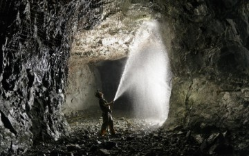 Image of a man spraying water in a mine