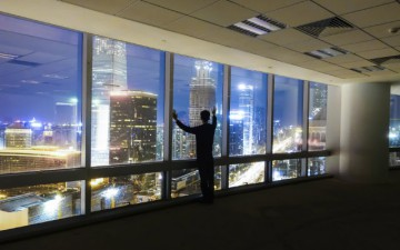 Image of a man standing in front of a window with a cityscape at night
