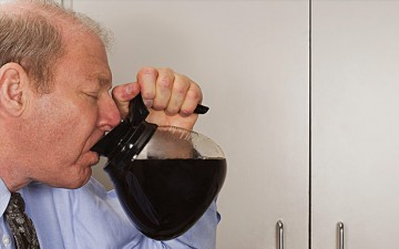 Image of a man drinking from a coffee pot
