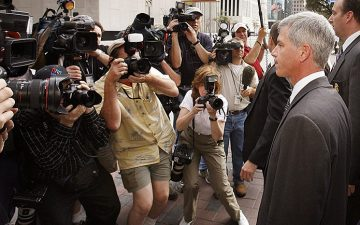 Image of Andy Fastow surrounded by the press