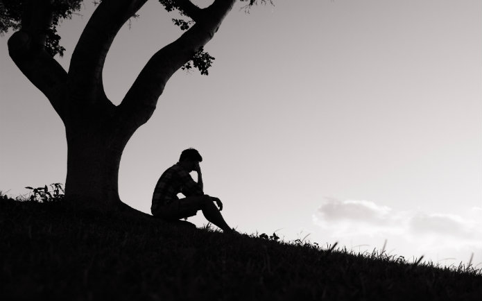 Silhouette of a man thinking near a tree