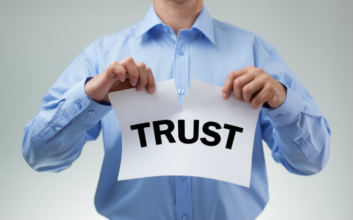 "Image of a man ripping a paper that says ""trust"""