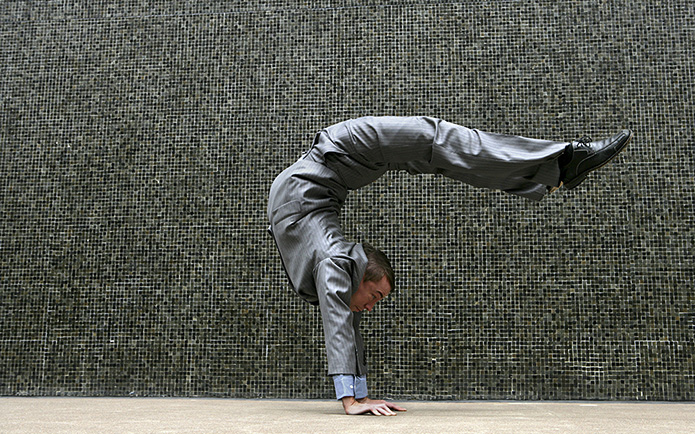 Businessman in a grey suit doing a handstand outdoors