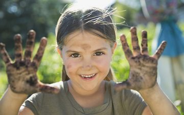 Image of a girl holding her dirty hands towards the camera