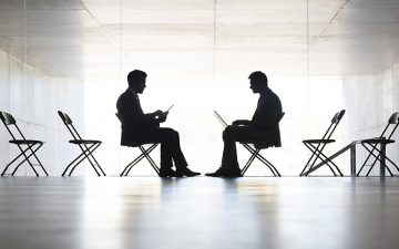 Silhouette of businessmen working in office, sitting across from each other