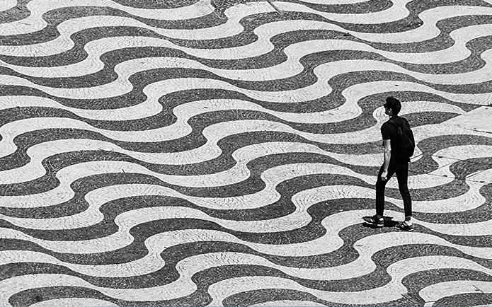 Black and white image of a man walking on a street with wavy lines