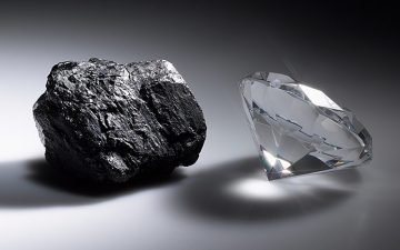 A black and white image of a piece of coal next to a diamond