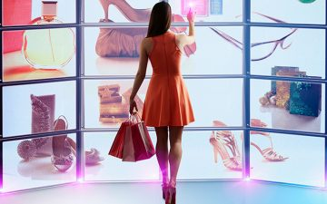 A woman in an orange dress standing in front of a shopping screen