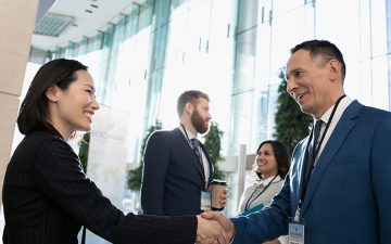 An Asian woman shakes hands with a white man