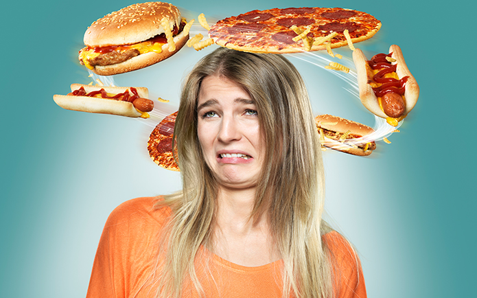 Image of a distressed woman with fastfood circling her head