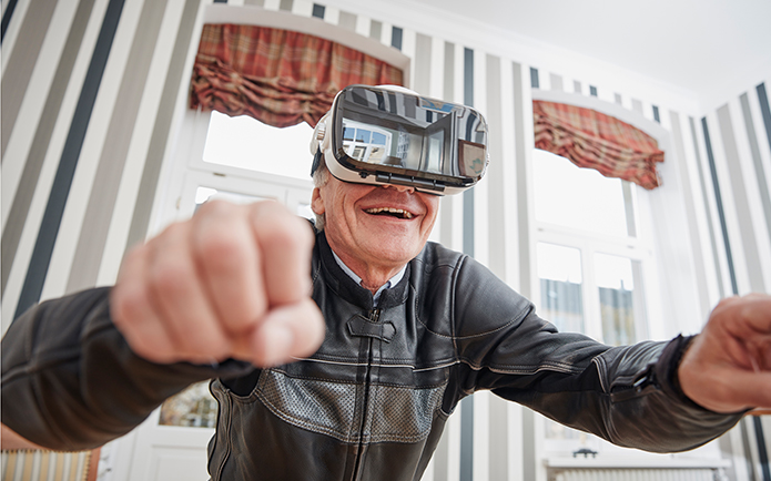 Image of an older man wearing a VR headset and smiling