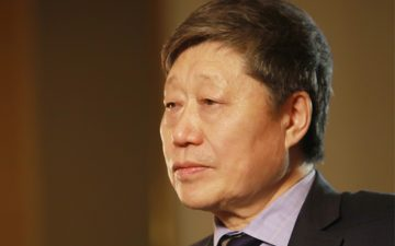 Image of an older Asian man frowning