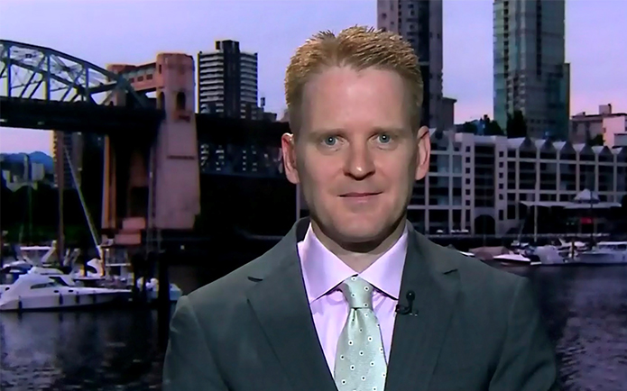 Image of a red haired man with a green tie looking into the camera