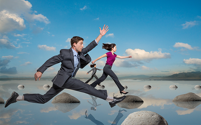 Image of business people leaping on rocks in a lake