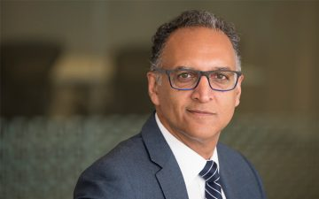 Older brown man with purple glasses smiles quietly at the camera