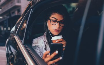 Woman sitting in a car listening to music looking at her phone with a cup in her hand