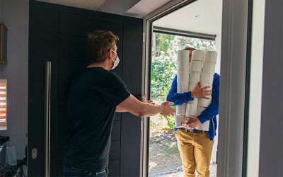 Man delivering huge pile of toilet rolls to customer in mask