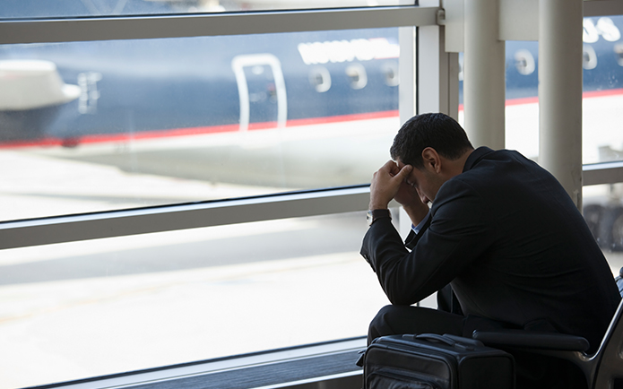 Frustrated Hispanic business traveler waiting in airport